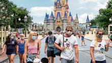 Doors open: Guests wear masks as required to attend the official reopening of the Magic Kingdom at Walt Disney World in Florida on Saturday. Photo: Joe Burbank/Orlando Sentinel via AP