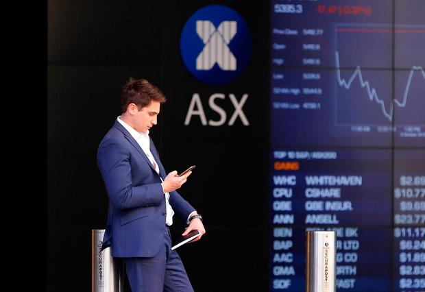 An investor reacts as he looks at his phone in front of a board displaying stock prices at the Australian Securities Exchange (ASX) in Sydney, Australia. Photo: Reuters
