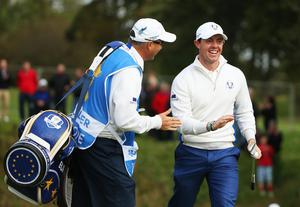 Rory McIlroy of Europe laughs alongside Terry Mundy, caddie for Ian Poulter of Europe during the morning fourballs