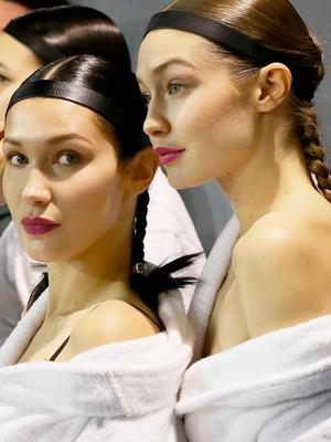 (L-R) Bella Hadid and Gigi Hadid prepare backstage before the  H&M Studio show as part of the Paris Fashion Week on March 1, 2017 in Paris, France.  (Photo by Vittorio Zunino Celotto/Getty Images)