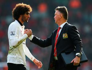 Manchester United manager Louis van Gaal celebrates with Marouane Fellaini after their victory over Liverpool at Anfield