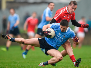 Dublin's Robert Gaughan his the turf, under pressure from Louth's Jim McEneaney, during yesterday's O'Byrne Cup final in Drogheda. Photo: Sportsfile