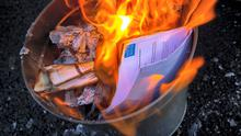 A water bill is burned at a protest. Photo: James Connolly / PicSell8