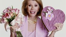 Portrait of American comedian Joan Rivers dressed in a pink suit as she holds a bouquet of roses and a heart-shaped box of candy, New York, New York, 1999. (Photo by Janette Beckman/Getty Images)