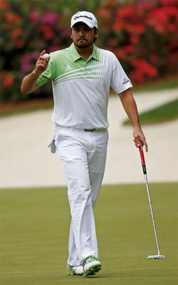 Jason Day of Australia holds up his ball after sinking a birdie putt on the 13th green