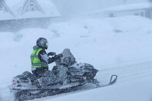 A Depew firefighter uses a snowmobile to travel down Transit Road (AP Photo/The Buffalo News, Derek Gee)