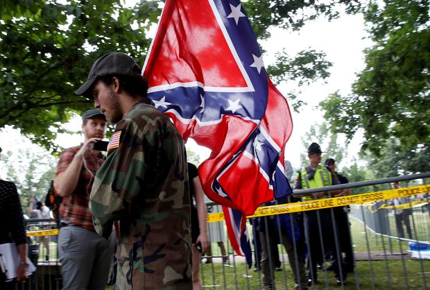 A white supremacists carries the Confederate flag as he arrives for a rally in Charlottesville, Virginia, U.S., August 12, 2017. REUTERS/Joshua Roberts