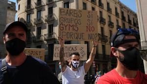 """A man holds a placard during a protest of gym staff and users over the closure of gyms as part of the restrictions to contain the spread of the coronavirus disease (COVID-19), at the San Jaume square, in Barcelona, Spain. Placard reads: """"Bars yes, groups yes, gyms not. Why not?"""". Photo: REUTERS/Nacho Doce"""