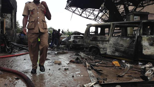 A fire services officer walks at the wreckage of a gas station that exploded overnight killing around 90 people in Accra, Ghana, June 4, 2015. REUTERS/Matthew Mpoke Bigg