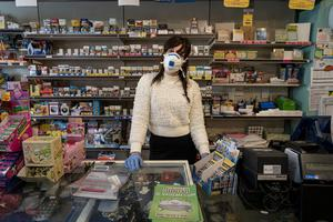 Masked up: Silvia waits for customers in a tobacconist in San Fiorano, a town on lockdown in northern Italy. Photo: Marzio Toniolo via REUTERS