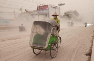A man wears a mask as he rides a becak, a kind of rickshaw, on a road covered with from Mount Kelud,  in Yogyakarta February 14, 2014. Mount Kelud volcano erupted late on Thursday night on the heavily populated Indonesian island of Java, sending a huge plume of ash and sand 17 km (10 miles) into the air and forcing the closure of three airports.