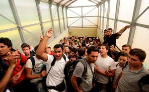 Migrants shout slogans after being stopped in Bicske, Hungary, Thursday, Sept. 3, 2015. Over 150,000 migrants have reached Hungary this year, most coming through the southern border with Serbia. Many apply for asylum but quickly try to leave for richer EU countries. (AP Photo/Petr David Josek)