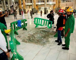 Members of an emergency crew stand near damage caused by a collapsed crane at the Grand Mosque in the Muslim holy city of Mecca, Saudi Arabia September 11, 2015. At least 107 people were killed when a crane toppled over at Mecca's Grand Mosque on Friday, Saudi Arabia's Civil Defence authority said, less than two weeks before Islam's annual haj pilgrimage. REUTERS/Stringer