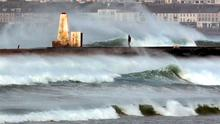 A man and dog walk along the wall at the Barmouth on Castlerock beach in Co-Derry as heavy seas and Autumn gales sweep along the north coast of Northern Ireland. Picture Margaret McLaughlin ©
