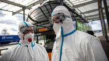 Health workers wear a protective mask and suit as they stands next to a bus to screen passengers temperature at the German-Polish border in Swiecko, Poland. Photo: Maja Hitij/Getty Images