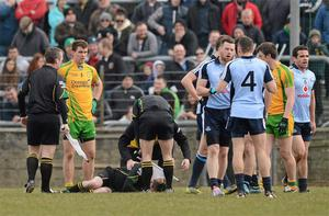 Referee Padraig Hughes lies on the pitch after twisting his ankle during the match between Dublin and Donegal