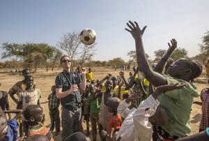 Goal CEO Barry Andrews plays football with children