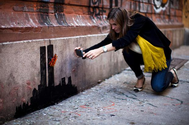 A woman takes a picture of an artwork by British graffiti artist Banksy at Lower Manhattan