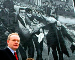 Martin McGuinness walking past a Bloody Sunday mural in the Bogside in Co Derry. Photo: Paul Faith/PA Wire