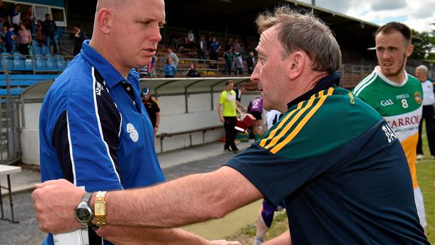 Waterford manager Tom McGlinchey, left, shakes hands with Offaly manager Pat Flanagan after the game