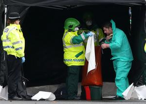A man is washed down at the scene at Gideon Court in Bathgate, West Lothian, after a nursery nearby was closed as a precaution following an incident. Andrew Milligan/PA Wire
