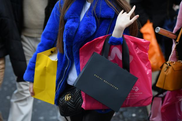A shopper carries her bags on Oxford Street in central London on December 21, 2019 on the last Saturday before Christmas. (Photo by DANIEL LEAL-OLIVAS / AFP)