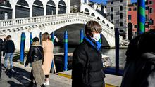 Bridge of sighs: A visitor wears mask at the Rialto Bridge in Venice, usually mobbed by tourists. Photo: Claudio Furlan