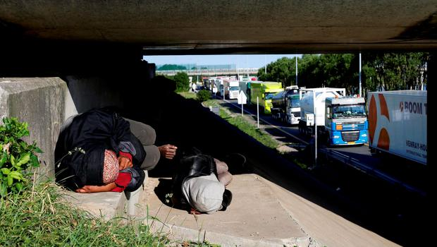 Migrants sleep along a motorway leading to a ferry port to cross the English Channel, in Calais, northern France. Photo: AP