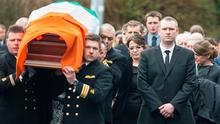 Hermione Duffy, wife of Coast Guard Captain Mark Duffy, walks behind the coffin of her husband at his funeral Photo: Mark Condren