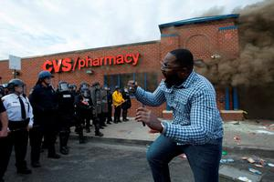 A man shouts in front of a police line beside a CVS pharmacy that caught on fire after being looted, as protests of the death of Freddie Gray continue. Photo: EPA