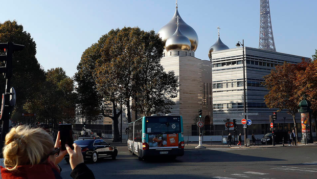 A woman takes a photo of the new Russian Orthodox Cathedral in Paris, with the Eiffel Tower in the background