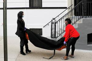 Sign of the times: Funeral home staff Alisha Narvaez and Nicole Warring carry a dead person into the basement area of their business in Harlem, New York, where bodies are prepared for funeral services amid a huge problem with storage capacity. Photo: REUTERS/Andrew Kelly