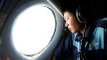 Military officer Nguyen Tran looks out from a Vietnam Air Force AN-26 aircraft during a mission to find the missing Malaysia Airlines flight MH370, off Con Dao island. Reuters