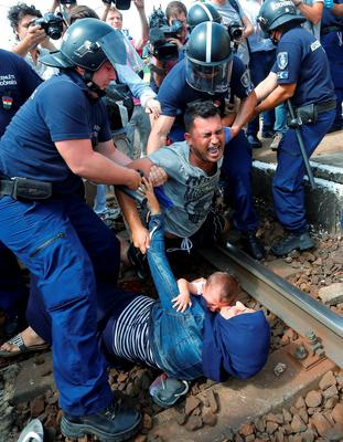 Hungarian policemen detain migrants on the tracks as they wanted to run away at the railway station in the town of Bicske, Hungary, September 3, 2015. A camp for refugees and asylum seekers is located in Bicske.         REUTERS/Laszlo Balogh