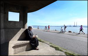 Sr. Anne from the Little Sisters of the Poor in Clontarf reading a book on Dollymount Strand during the warm weather