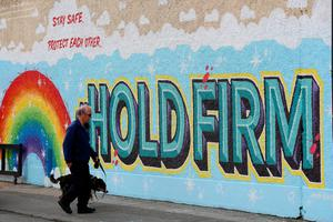 A man walks his dog past a new mural in Dublin's city centre inspired by the new HSE 'Hold Firm' campaign which took it's inspiration from a poem by President of Ireland Michael D Higgins. Photo: Brian Lawless/PA Wire