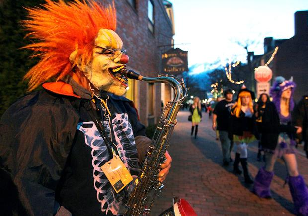 SALEM, MA - OCTOBER 31: The scene on Halloween evening in downtown Salem included Joe Cotreau playing his saxophone for tips while wearing a scary clown mask. (Photo by Jim Davis/The Boston Globe via Getty Images)