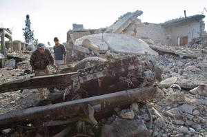 In this Wednesday, Nov. 19, 2014 photo, a Kurdish People's Protection Units (YPG)  fighter shows the extent of the damage from a truck bomb in Kobani, Syria. (AP Photo/Jake Simkin)