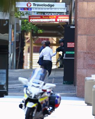 Two hostages run to safety outside the Lindt Cafe, Martin Place on December 15, 2014 in Sydney, Australia.  Police attend a hostage situation at Lindt Cafe in Martin Place.  (Photo by Mark Metcalfe/Getty Images)