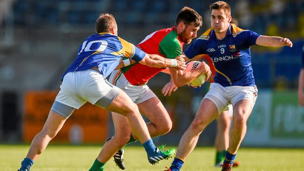 Carlow's Eoghan Ruth breaks through a challenge from Kevin Diffley and Peter Foy, left