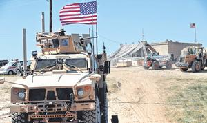 Going home: A US soldier sits on an armoured vehicle in Manbij, north Syria. Photo: Hussein Malla/PA