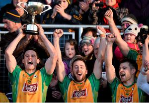 Corofin captain Michael Farragher, left, lifts the Shane McGettigan cup, as he celebrate's with team-mate's Michael Lundy, centre and Cathal Silke.