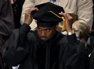 Musician Kanye West adjusts his cap before receiving an honorary doctorate degree from School of the Art Institute of Chicago during their annual commencement ceremony in Chicago, Illinois, May 11, 2015. REUTERS/Jim Young