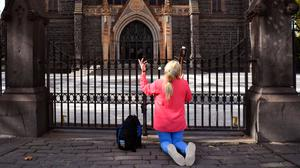 Locked down and locked out: A woman prays outside the closed St Patrick's Catholic Cathedral in Melbourne. Photo: Getty Images