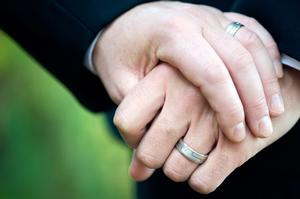 This image shows two men holding hand displaying their wedding rings.