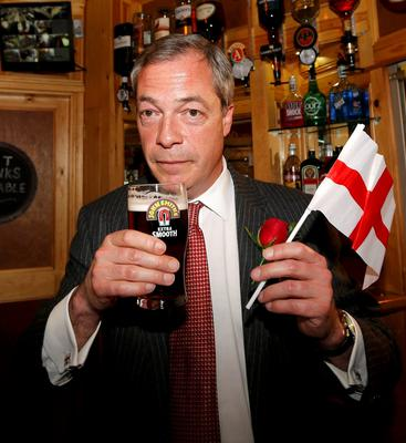 Sign of Britain's uneasy gut: Ukip leader Nigel Farage holds a flag bearing a St George's Cross as he enjoys a pint of beer on St George's day