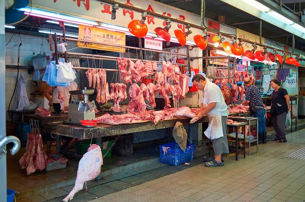 A man at work in a Chinese meat market. Stock photo