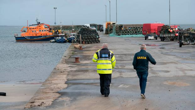 Gardai approaching the Ballyglass lifeboat changing crew to continue the search for a Coast Guard Helicopter Missing at Blacksod Pier, Belmullet, Co. Mayo. Photo : Keith Heneghan / Phocus