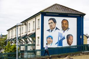 A man walks past the Bogside mural in Derry City of John Hume, Martin Luther King Jr, Mother Teresa, and Nelson Mandela. Photo: Liam McBurney/PA Wire