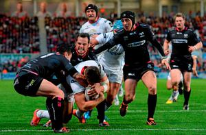 Stuart McCloskey, Ulster, goes over for his side's second try despite the efforts of Tom Graham and Dan Evans, Ospreys